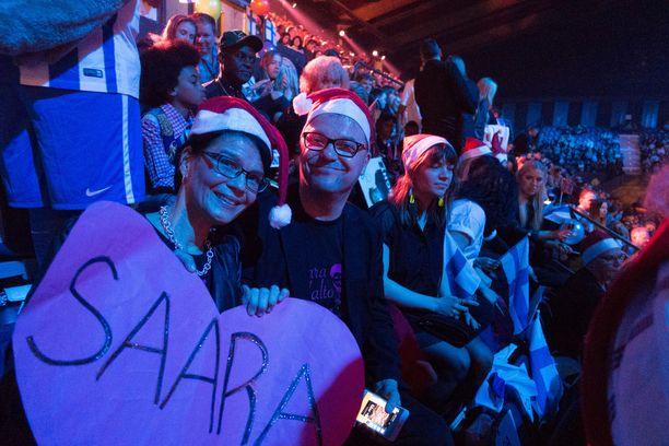 Saara Aallon vanhemmat Taina ja Markus Aalto kannustivat tytärtään yleisössä ison sydämellisen kyltin kera.