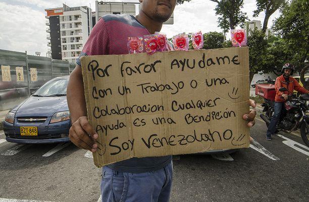 Venezuelalaismies kerjäsi rahaa tai töitä Kolumbiassa kaksi viikkoa sitten. Maahan on jo paennut reilut puoli miljoonaa venezuelalaista.
