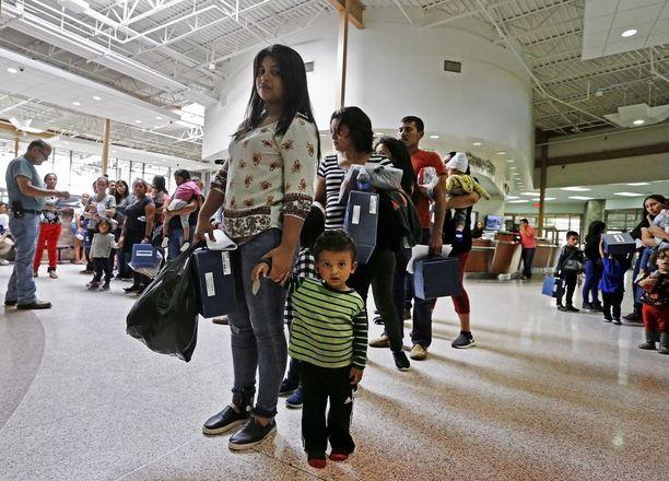 Siirtolaisperheitä linja-autoasemalla, josta matka jatkui katolisen hyväntekeväisyysjärjestön tiloihin Texasin McAllenissa.