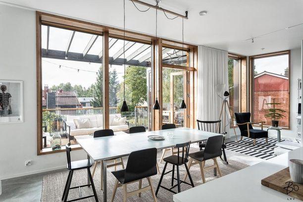 Yksi hyvä esimerkki nykyasumisesta on myös tämä: kesäisin sisätiloja jatketaan ulos ja sisustetaan huoneenomaisesti. Tässä lasiterassi avautuu heti ruokailutilan viereen.