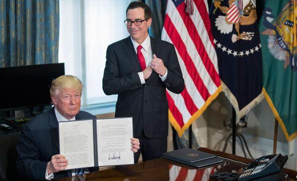 Donald Trump pitelee allekirjoittamiaan määräyksiä, Mnuchin hymyää taustalla.