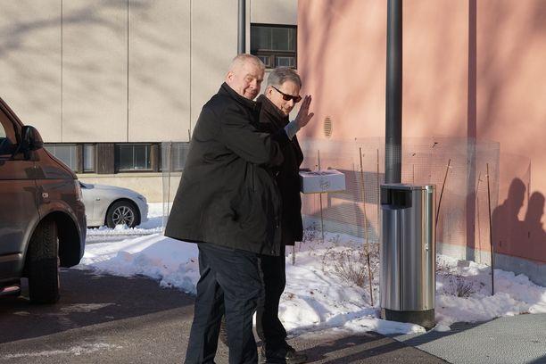 Hyväntuulinen Sauli Niinistö vilkutti kakku kädessään valokuvaajille.