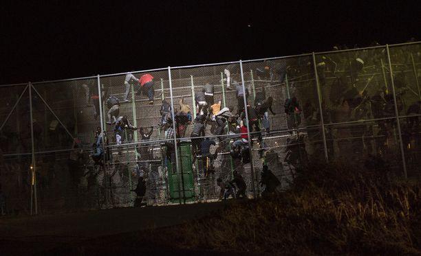 Arkistokuvassa Marokosta tulevat pakolaiset pyrkivät aidan yli Espanjan maaperälle. Suomessa suojelupoliisi on varautunut turvapaikanhakijoiden määrän huomattavaan kasvuun.