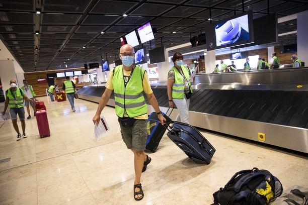Berliinissä sijaitsevan uuden Brandenburgin lentokentän testikäyttäjät hakevat laukkujaan hihnalta 28. heinäkuuta 2020.