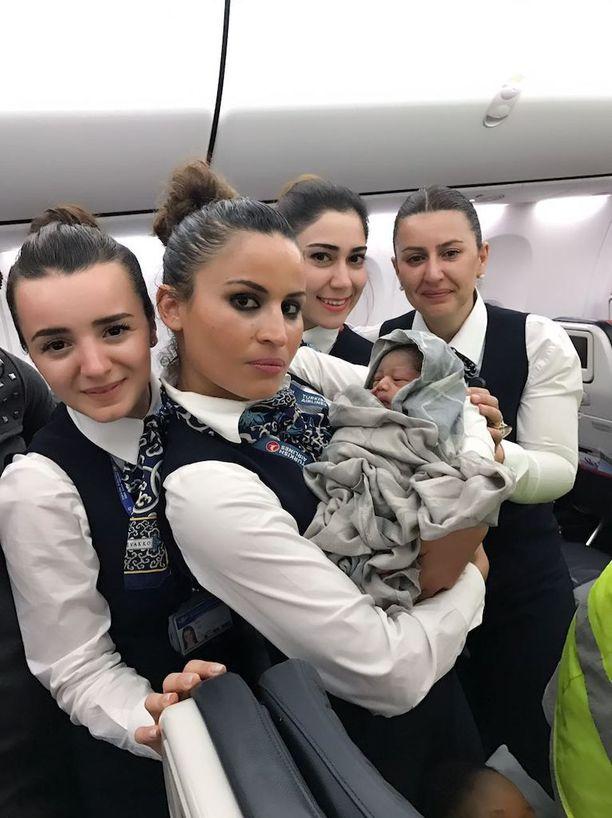 Synnytyksessä tiimityötä tehneet lentoemännät poseerasivat vastasyntyneen kanssa.