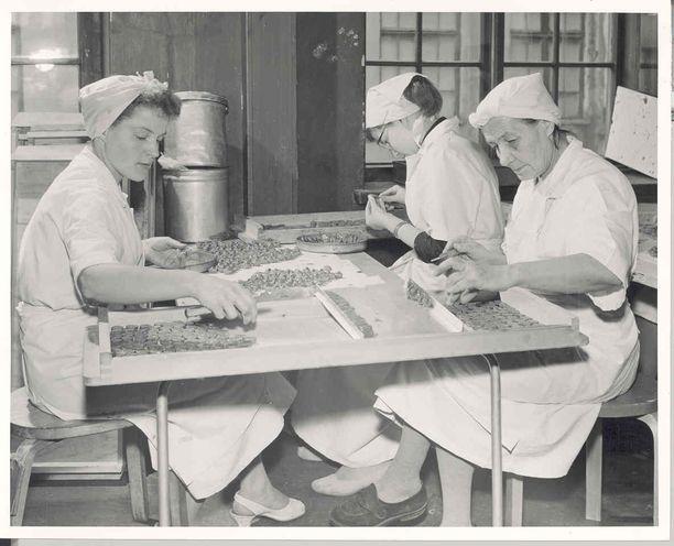 Suklaakonvehteja valmistetaan käsin 1950-luvulla.