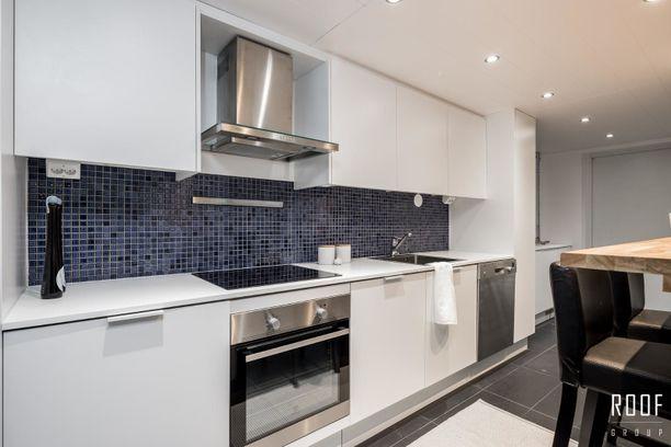 Asunnossa on valkoinen minimalistinen keittiö.