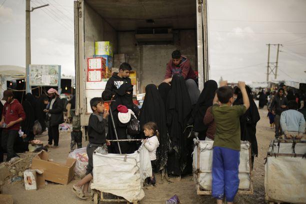 Naiset ja lapset ostivat kuorma-auton takaosasta tarvikkeita ja ruokaa al-Holissa maaliskuussa.