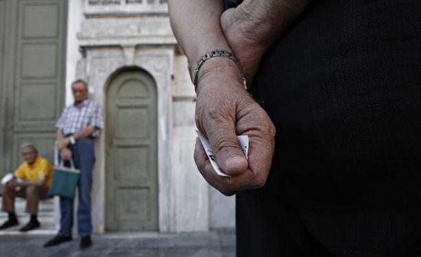 Kreikan eläkeläiset jonottavat eläkkeitään pankin oven takana.