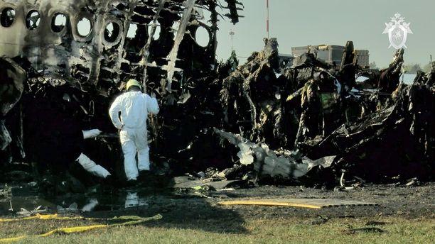 Kuvakaappaus Venäjän onnettomuustutkintakomitean videolta. Koneen palaneilla raunioilla tutkimukset onnettomuussyystä jatkuivat sunnuntaina.