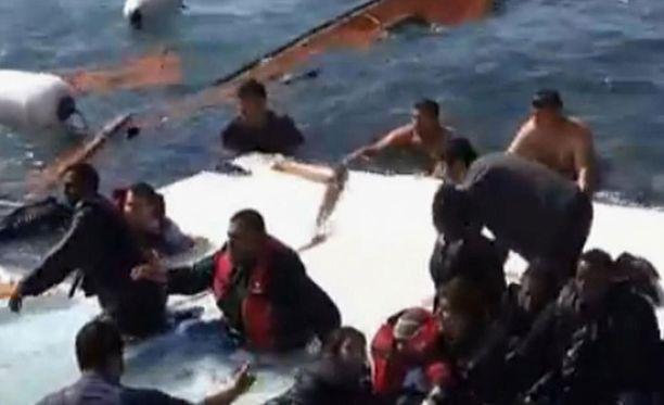 Pelastustyöntekijät auttavat matkustajia pääsemään turvaan.