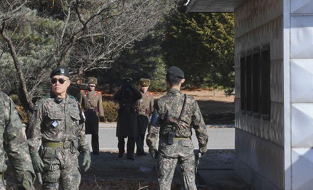 Pohjois-Korean sotilaat tiirailevat kiikareilla Etelä-Korean puolelle Etelä-Korean sotilaiden seistessä vartiossa demilitarisoidulla vyöhykkeellä. Kuvituskuva.