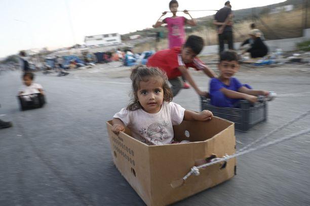 Pakolaislapset leikkivät tiellä, jonka lähellä sijaitsee viime viikolla tulipalossa tuhoutunut Morian pakolaisleiri.