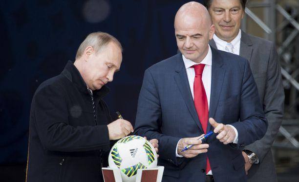 Vladimir Putin kirjoitti nimikirjoituksensa jalkapalloon Moskovassa keskiviikkona. Etualalla oikealla Fifan puheenjohtaja Gianni Infantino.