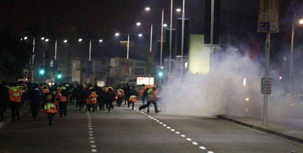 Mielenosoittajat pakenivat kyynelkaasupilviä.