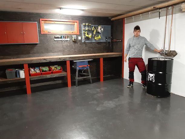 Mikko Tuomi uudessa autotallissa, jossa on dynaaminen värimaailma. Katseenvangitsija on netistä ostettu oluttynnyri. Koko seinän levyinen työtaso on kätevä.