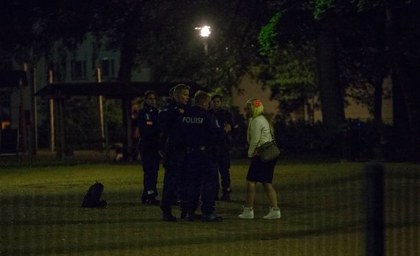 Poliisi puhutti illanviettäjiä puistossa.
