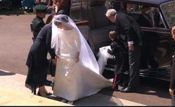 Meghan Marklen asu on elegantti ja siinä on pitkä laahus. Päässään hänellä on Elisabetilta lainattu tiara.