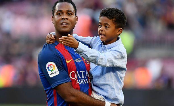 Patrick Kluivert nosti poikansa Shanen syliinsä Barcelonan legendojen ottelun jälkeen.