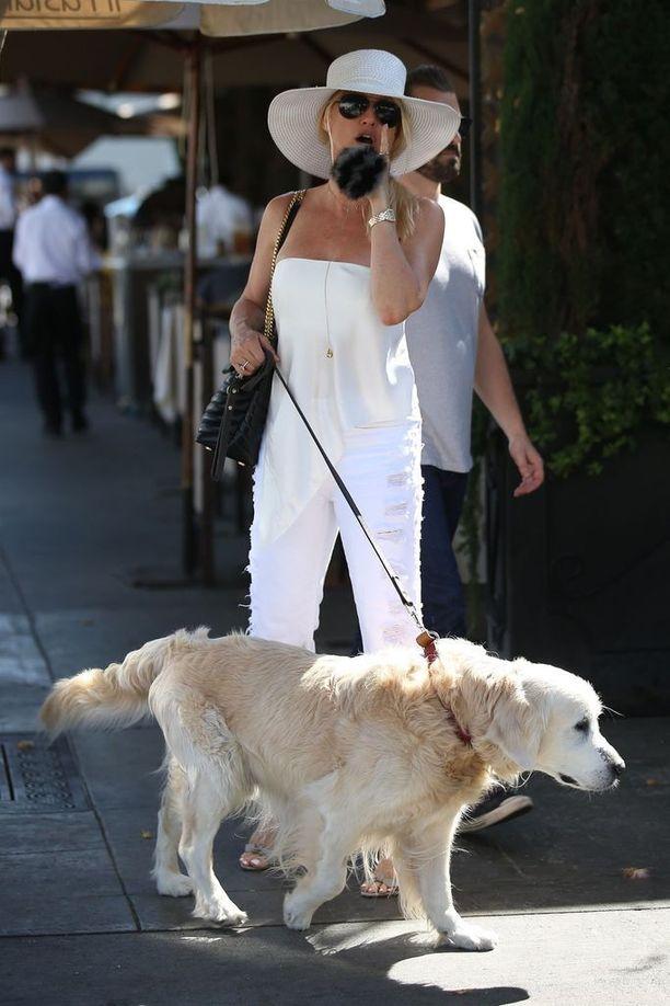 Näyttelijä Nicollette Sheridan luottaa kokovalkoiseen asuun. Elegantin tyylin kruunaa vaalea hattu.
