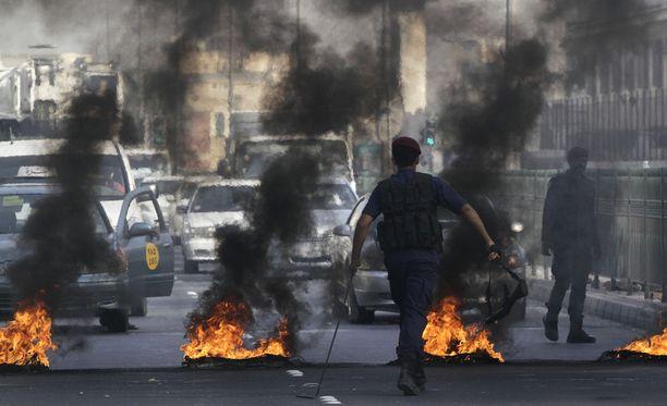 Bahrainilainen mellakkapoliisi käveli kohti palavia autonrenkaita.