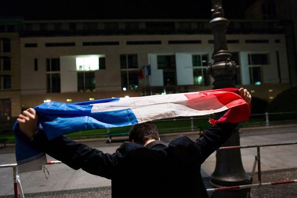 Mies nosti lipun ilmaan Ranskan lähetystön edustalla Berliinissä.