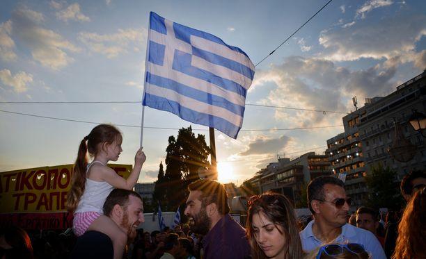 Pieni tyttö heilutti Kreikan lippua isänsä olkapäillä maanantai-illan mielenosoituksessa.