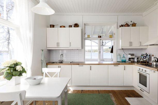 Tätä kokovalkoista keittiötä piristävät sisustuksen vihreät yksityiskohdat. Vihreä on ollut trendiväri sisustuksessa tänä vuonna.