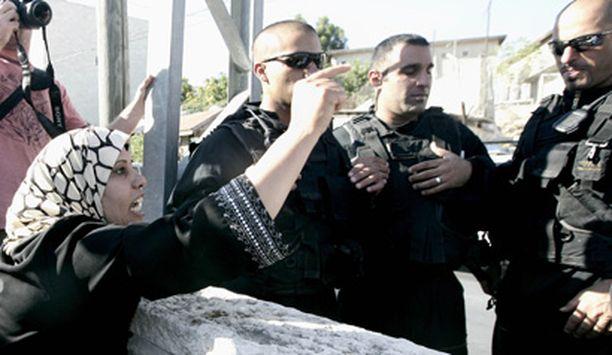 Kodistaan häädetty palestiinalaisnainen raivoaa mellakkapoliiseille.