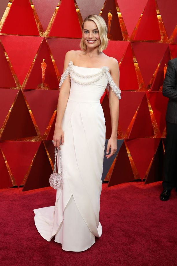 Margot Robbie edusti yksinkertaisessa valkoisessa iltapuvussa. Robbie on ehdolla roolityöstään elokuvassa I, Tonya.