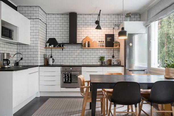 Tämän keittiön koko seinä on toteutettu tiililadonnalla. Yläkaappien sijaan avohyllyillä voi säilyttää kaiken kauniin ja tarpeellisen.