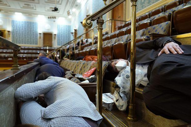 Ihmisiä kyyhötti piilossa tunkeutujien pyrkiessä kongressin istuntosaliin Washingtonissa keskiviikkona.