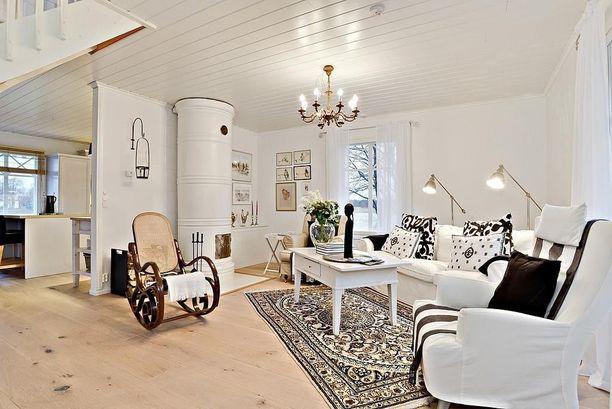 Pönttöuuni, vaaleat puulattiat ja paljon lämmintä valoa. Siinä onnistuneen hyggetunnelman konsepti. Vaalea itämainen matto tuo oman tunnelmalisänsä.