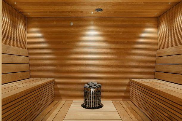 Vastakkain asetellut penkit ja lamput katossa tuovat ripauksen kylpylämäistä tunnelmaa muuten melko perinteiseen saunaan.