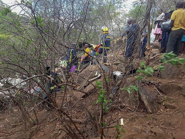 Pelastushenkilökunta käy läpi pudonneen koneen jäännöksiä.