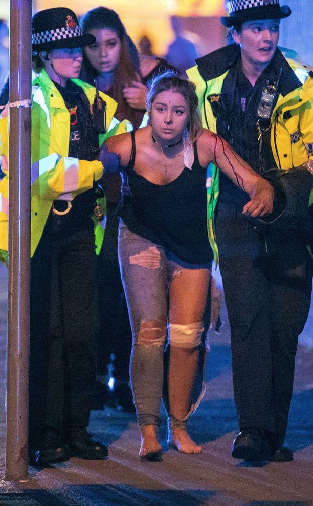 Poliisi talutti nuorta naista ulos iskun tapahtumapaikalta. Kuva nousi maailman sanomalehtien kansiin.
