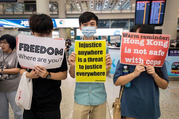 Mielenosoittajat näyttivät kylttejään Hongkongin lentokentällä.