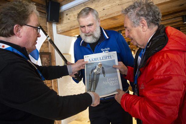 Olli Pöllänen (vas.) ja Juha Mieto antoivat vanhalle tutulleen Kurt Matzille nipun suomalaisia lehtiä. Matz ihaili Aamulehden kantta, ossa Nykänen hyppäsi Kneisslin suksilla.