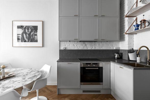 Tämä kaupunkikodin keittiö on nykyisten trendien mukainen värimaailmaltaan. Nyt keittiöissä nähdään mudan eri sävyjä ruskeasta harmaaseen. Kiiltävien kaappien ja kiintokalusteiden sijaan suositaan mattapintaisia kalusteita. Eläväpintaisilla kivimateriaaleilla saadaan keittiöön omantakeisuutta.