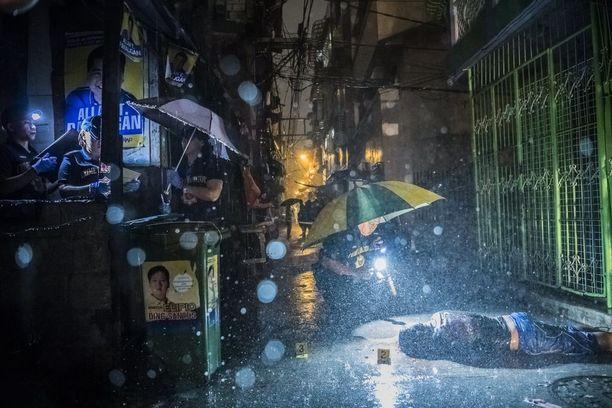 HE TEURASTAVAT MEITÄ KUIN ELÄIMIÄ Rankkasade huuhteli kujaa, jolla Romeo Joel Torres Fontanilla, 37, sai surmansa. Kaksi moottoripyörällä liikkunutta tuntematonta asemiestä ampui hänet varhain aamulla Manilassa.