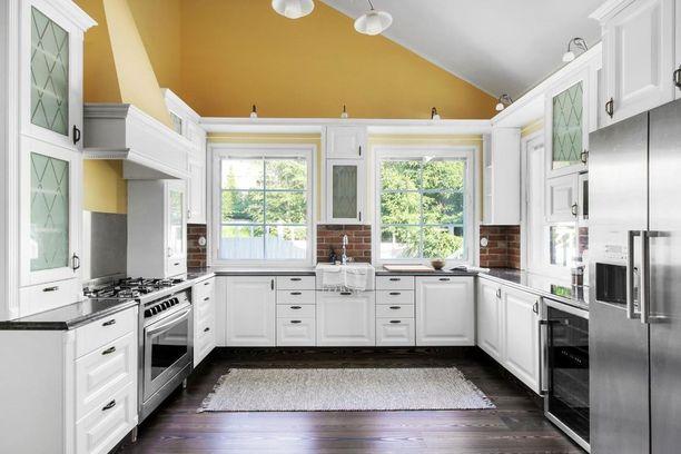 Valkoiset keittiökaapit sopivat kauniisti yhteen tumman lattian ja keltaisen seinän kanssa.