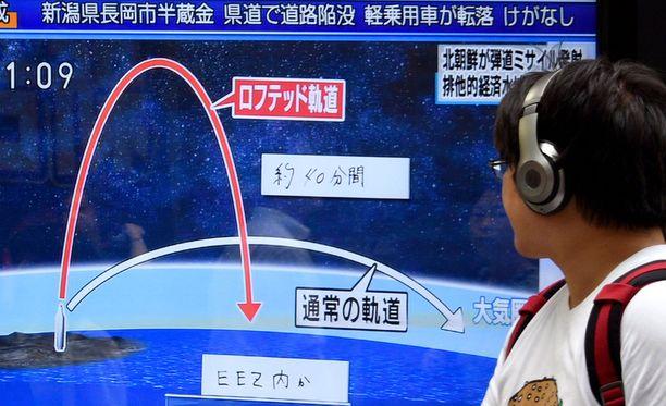 Jalankulkija katsoi kadulla Pohjois-Korean ohjuskokeesta kertovaa uutislähetystä Japanin pääkaupungissa Tokiossa. Japani on tuominnut ohjuskokeen.