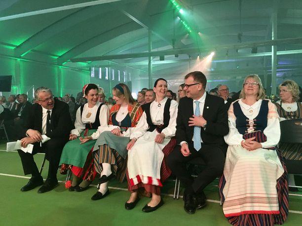 Juha Sipilän vaimo Minna-Maaria Sipilä pukeutui sunnuntaina kansallispukuun. Myös varapuheenjohtajat Katri Kulmuni ja Hannakaisa Heikkinen vaalivat perinteitä. Sipilä ja Juha Rehula edustivat tummissa puvuissa.