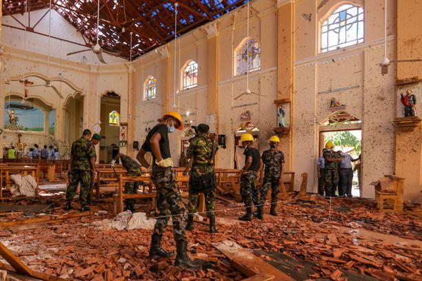 Sotilaat tutkivat pommi-iskun jälkiä kirkossa Negombossa, noin 30 kilometrin päässä pääkaupungista Colombosta.