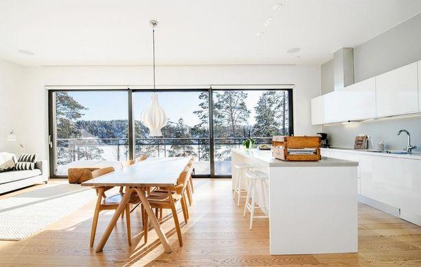 Tämän keittiön valo on taattu, koska yksi huoneen seinistä on pelkkää ikkunaa. Valoisuutta lisäävät myös vaaleat seinät ja katto sekä keittiön tasot ja kaapit.