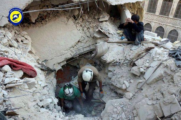 Vapaaehtoiset White Helmets -järjestön jäsenet etsivät ihmisiä tiistaina raunioista Aleppossa.