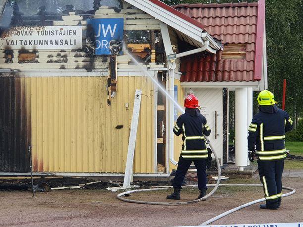 Palokunta sammuttaa tulen runtelemaa rakennusta.