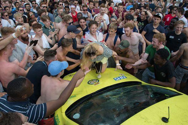 Kipuamisessa apua saanut nainen esitteli auton päällä rintaliivejään.