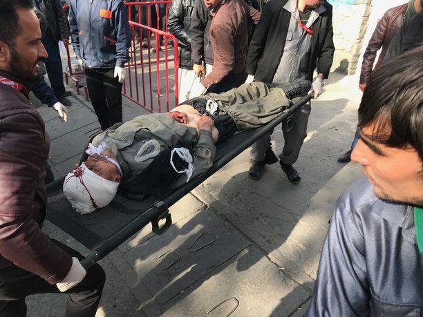 Pommi-iskussa haavoittunutta miestä kuljetettiin sairaalaan.