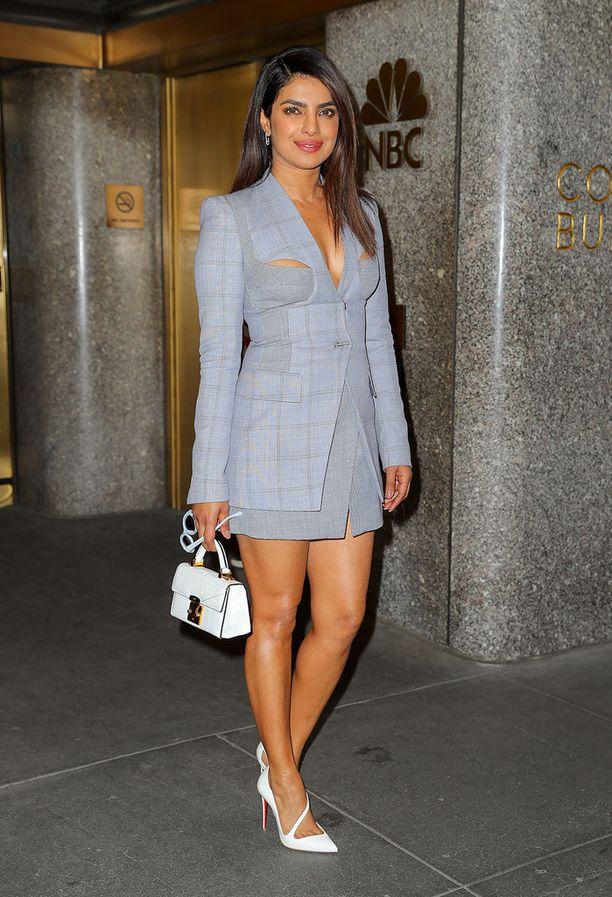 Priyanka Chopra piristää ruudullista jakkuasua seksikkäällä leikkauksella. Trendipisteitä irtoaa myös valkoisista kengistä ja pikkulaukusta.
